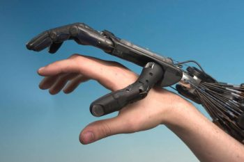 robot hand with human hand via Wikimedia