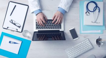An illustrative photo of a doctor on a computer. Photo by Pixabay