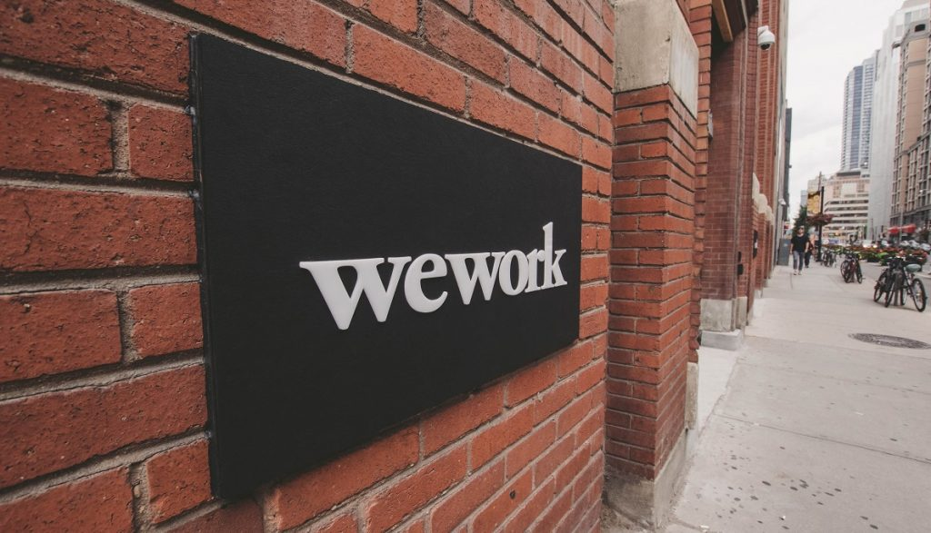 A WeWork sign. Photo by Eloise Ambursley on Unsplash