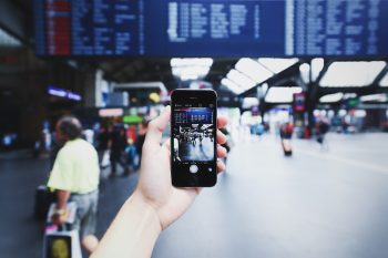 A person using a phone at a train station. Photo via Pexels