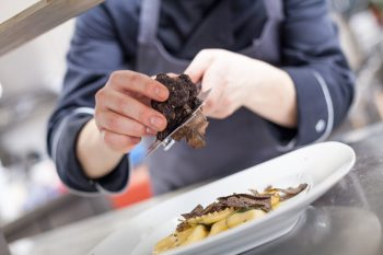 An illusrtrative photo of a chef grating truffle mushroom shavings onto homemade ravioli.