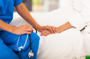 An illustrative photo of a doctor holding a patient's hand. Deposit Photos