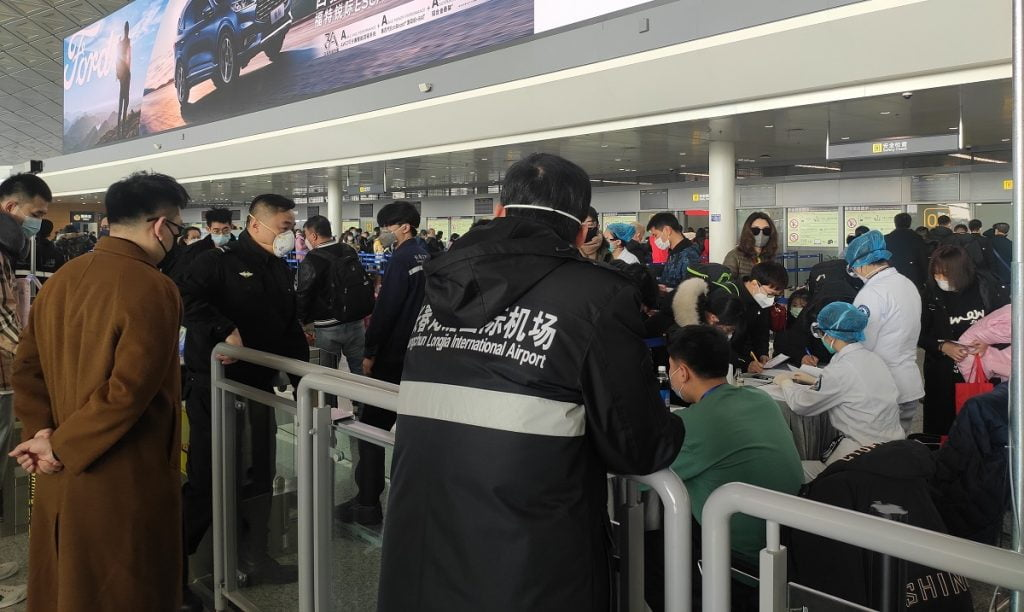Passengers wearing masks going through an extra body temperature check as part of airport security in northeast China's Changchun Longjia Airport, January 26, 2020. Wikimedia